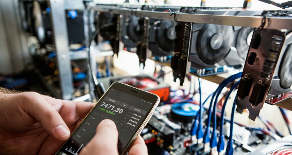 Cryptocurrency mining rig with man checking the Bitcoin price on a portfolio tracker app on a mobile phone. Cryptocurrency mining is one of the most popular ways to earn Bitcoin and other proof of work coins, it uses powerful computer hardware and processors to solve complex mathematical formulas which then create new coins.