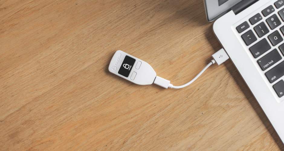 Trezor waller connected to a laptop via USB cable. The Trezor hardware wallet is a popular choice among cryptocurrency users to safely store their digital coins offline. Users must physically verify any transactions that happen when using a cryptocurrency hardware wallet.